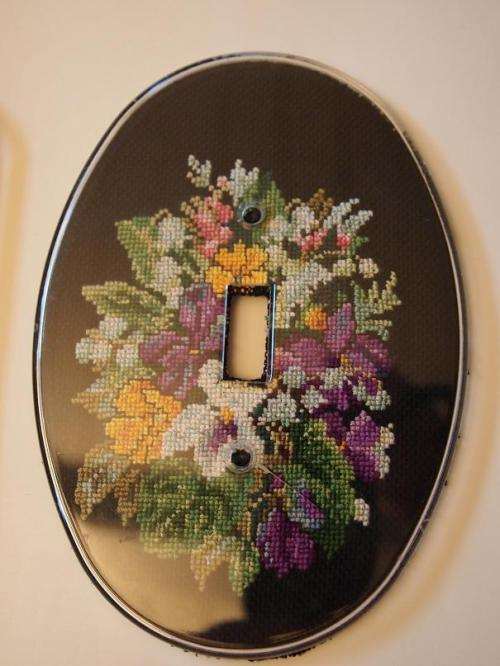 cross stitched light plate cover with flowers on black